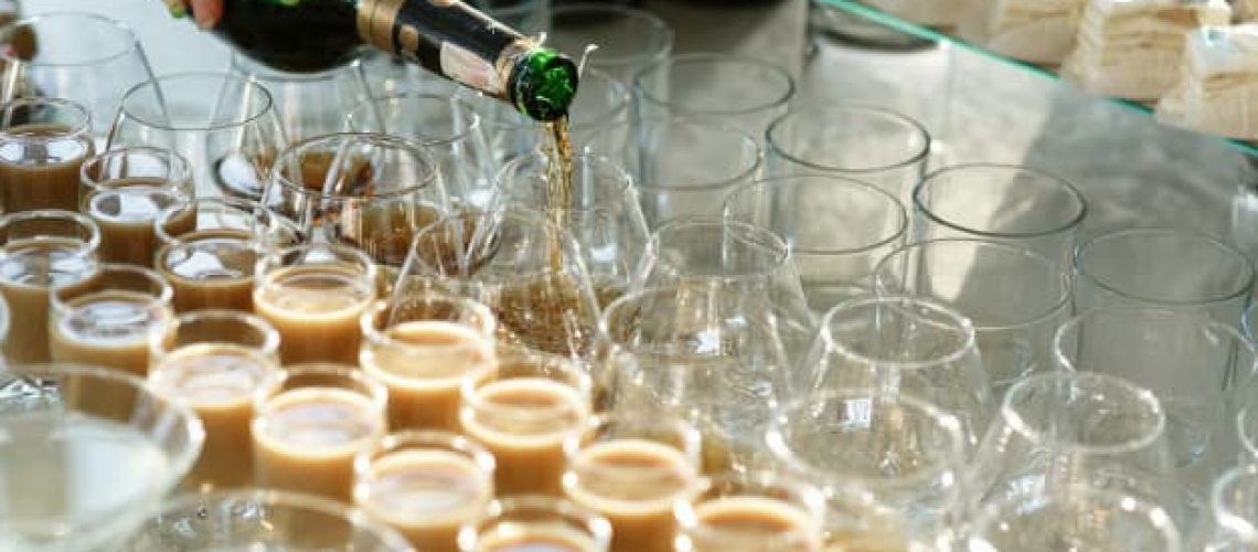 woman-pours-whisky-glasses-table-with-sweets-alcohol_8353-617